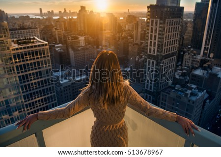 Rich woman enjoying the sunset standing on the balcony at luxury apartments in New York City. Luxury life concept. Successful businesswoman relaxing. Royalty-Free Stock Photo #513678967