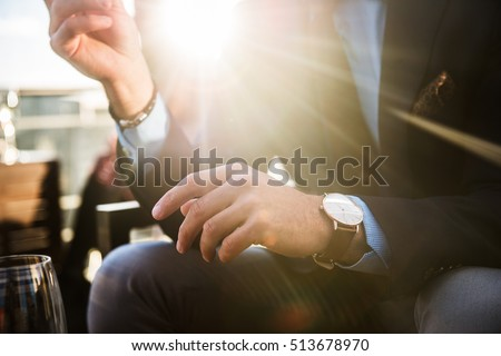 Lifestyle photo of elegant businessmen wearing luxury watch and having dinner in restaurant after succesful working day. Royalty-Free Stock Photo #513678970