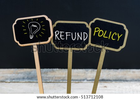 Concept message REFUND POLICY and light bulb as symbol for idea written with chalk on wooden mini blackboard labels, defocused chalkboard and wood table in background #513712108