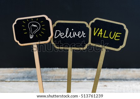 Concept message DELIVER VALUE and light bulb as symbol for idea written with chalk on wooden mini blackboard labels, defocused chalkboard and wood table in background #513761239
