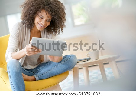 Mixed-race woman websurfing on digital tablet at home #513791032