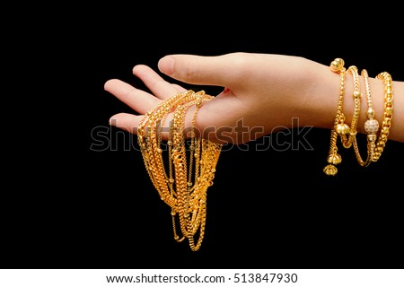woman's hand with many different gold jewelry on black background #513847930