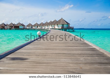 Lined up wooden bridge to the Water Bungalow over the blue ocean in Maldives #513848641