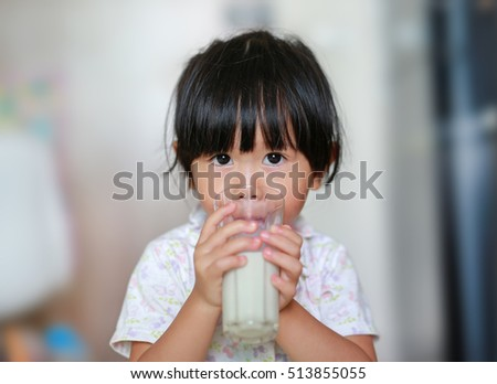Close up of little girl in pajamas drinking milk from glass indoor at the morning. #513855055