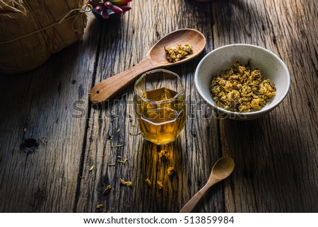 Focus Spot Chrysanthemum Tea and dried chrysanthemum on an old wooden table. Chrysanthemum blossoms are a type of herbal plants. In the morning, drink chrysanthemum Tea will make you feel refreshed. #513859984