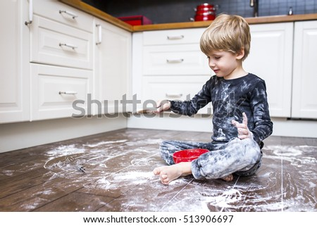 A boy sitting on the kitchen floor and playing with flour.  Royalty-Free Stock Photo #513906697
