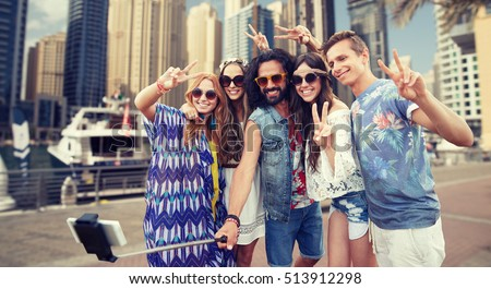 nature, summer, youth culture, technology and people concept - smiling hippie friends in sunglasses taking picture by smartphone on selfie stick and showing peace gesture over dubai city harbour