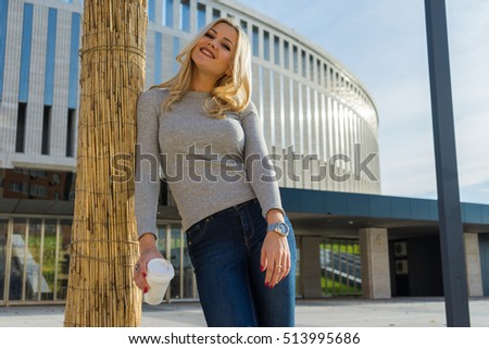 Beautiful attractive young blonde haired businesswoman with red lips and a white disposable coffee cup, drinking coffee against urban city background. Casual style, shining smile, sunny day. #513995686