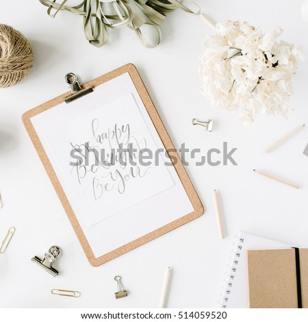 Flat lay, top view office table desk. feminine desk workspace with clipboard and inspirational quote, twine, pencils, floral bouquet, craft diary and clips on white background.