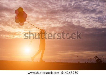 silhouette of young woman holding colorful of balloons with sunset #514363930