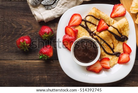 Fresh homemade crepes with strawberries and chocolate sauce on rustic wooden background. Top view. Royalty-Free Stock Photo #514392745