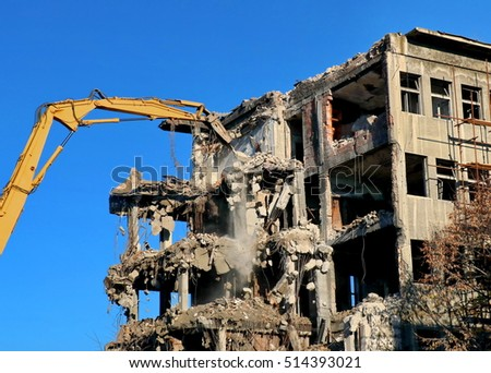 Building demolition with hydraulic excavator Royalty-Free Stock Photo #514393021