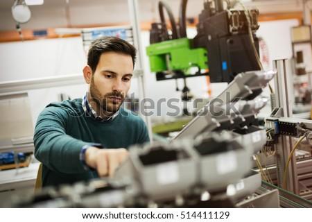 Creative mechanical engineer working on machines Royalty-Free Stock Photo #514411129