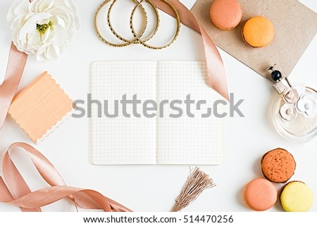 Blank notebook for ideas, macoroons, accesories, perfume bottle, flower and ribbon on a white background. Flat lay styling. Copy space #514470256