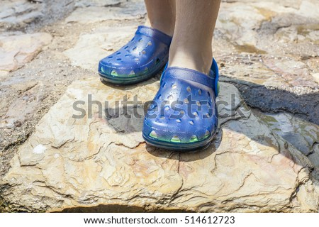 Little girl legs wearing her blue plastic clogs just after swimming #514612723