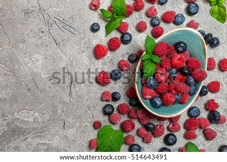 Fresh summer berries in vintage bowl over gray background,top view #514643491