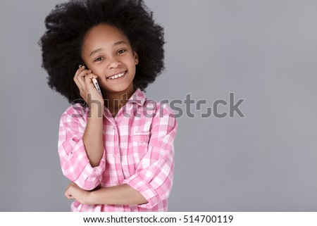 Cheerful mulatto girl speaking by mobile phone and smiling while standing against background #514700119