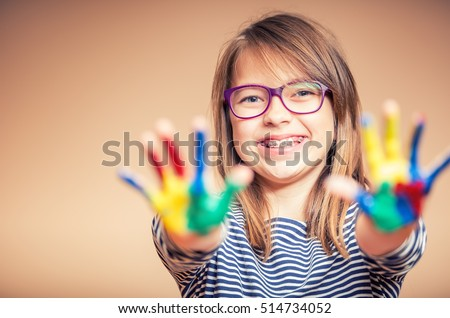 Portrait of a little pre-teen student girl showing painted hands. Girl with teeth braces and glasses. #514734052