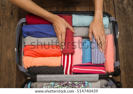woman packing a luggage for a new journey Royalty-Free Stock Photo #514740439