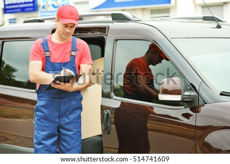 Delivery concept. Postman checking orders near a car #514741609