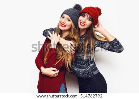 Two  cheerful young friends in perfect mood having time together on white isolate background. Wearing   trendy winter sweater and knitted red and grey hat . Positive and friendship concept.  #514762792