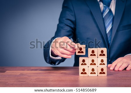 Human resources, social networking, assessment center concept, personal audit or CRM concept - recruiter complete team by one person. Employees are represented by wooden cubes with icons. Royalty-Free Stock Photo #514850689