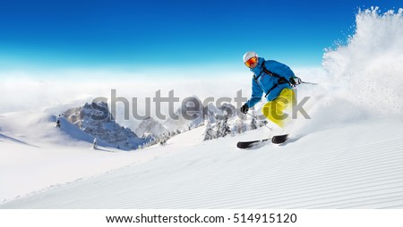 Skier on piste running downhill in beautiful Alpine landscape. Blue sky on background. Free space for text #514915120