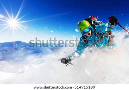 Freeride skier with rucksack running downhill in freeze motion of snow powder. #514915189