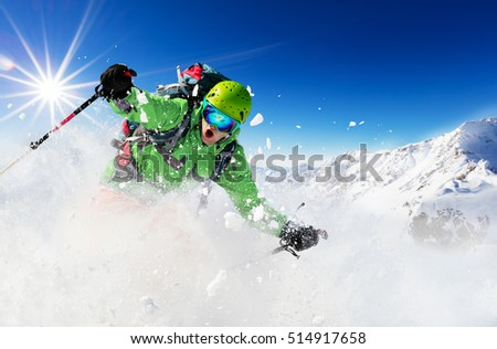 Freeride skier with rucksack running downhill in freeze motion of snow powder. #514917658