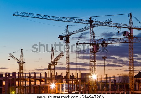 Silhouettes of tower cranes against the evening sky. House under construction. Industrial skyline Royalty-Free Stock Photo #514947286