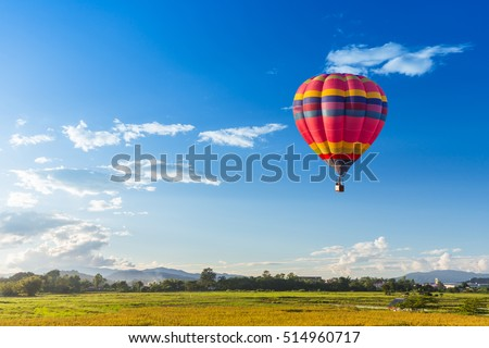 hot air balloon over the green paddy field. Composition of nature and blue sky background Royalty-Free Stock Photo #514960717