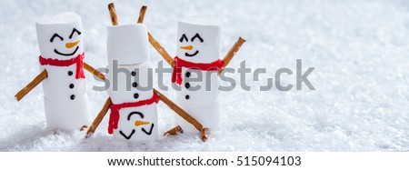 Happy funny marshmallow snowman are having fun in snow