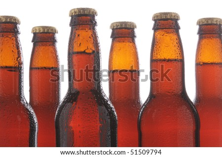Close up of six brown beer bottles with condensation. Horizontal format over a white background #51509794