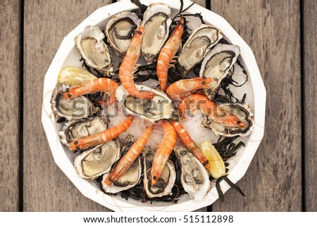 Fresh seafood plate with oysters and shrimps on wooden table., Old fashioned instagram style sepia colors.  #515112898