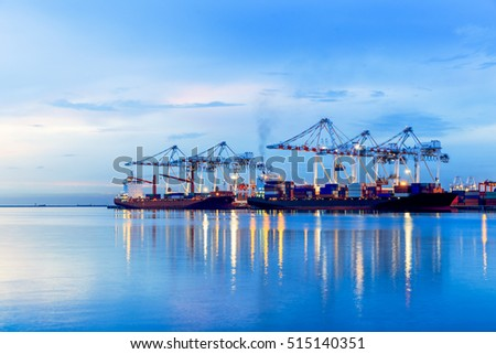 Container Cargo port freight ship with working crane bridge in shipyard at dusk for Logistic Import Export background, Containers loading by crane in the evening , Trade Port , Shipping #515140351