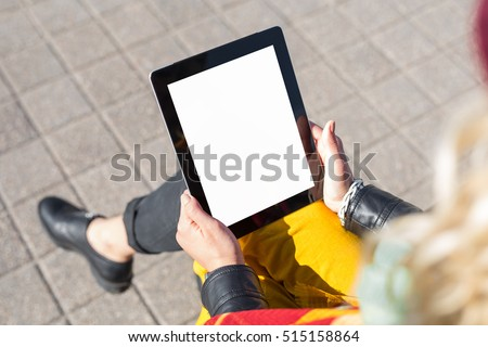 Woman sitting and using blank screen tablet