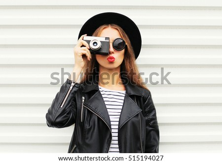 Fashion look, pretty cool young woman model with retro film camera wearing elegant black hat, leather rock jacket over white background