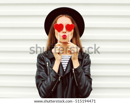 Fashion portrait pretty sweet young woman with red lips making air kiss with lollipop heart wearing black hat leather jacket over white background #515194471