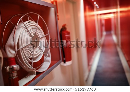 Fire extinguisher and fire hose reel in hotel corridor #515199763