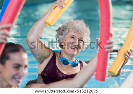 Smiling senior woman doing aqua fitness with swim noodles. Happy mature healthy woman taking fitness classes in aqua aerobics. Healthy old woman holding swim noodles doing aqua gym with young trainer. #515212096