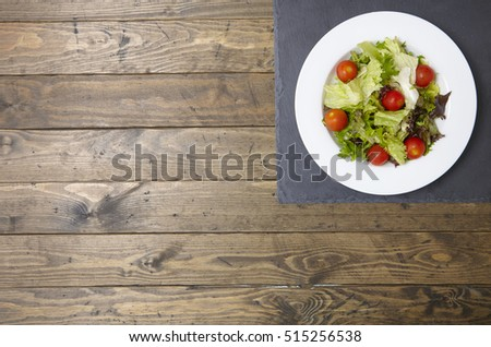 A bowl of fresh garden salad on a rustic wooden table top background, with empty space at side #515256538