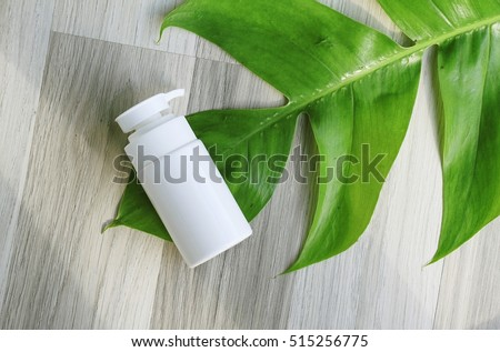 Cosmetic pump bottle containers with green herbal leaves, Blank label for branding mock-up, Natural beauty product concept. #515256775