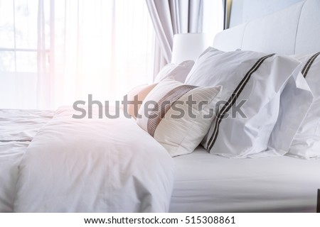 Bed maid-up with clean white pillows and bed sheets in beauty room. Close-up. Lens flair in sunlight. #515308861
