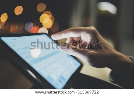 Closeup image of male hands typing on touch screen of modern digital tablet device at night, bokeh light in the blurred background, technology and social networking concept, man using tablet pc  #515369722