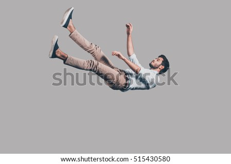 Man falling down. Mid-air shot of handsome young man falling against grey background  Royalty-Free Stock Photo #515430580
