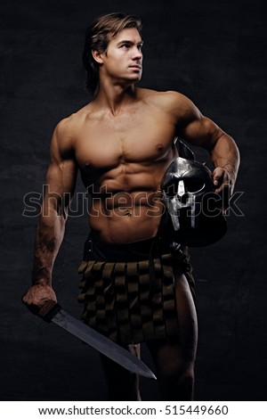 Portrait of shirtless muscular male in a Rome soldier costume holds silver gladiator helmet and an iron sword in a contrast dramatic studio light. #515449660