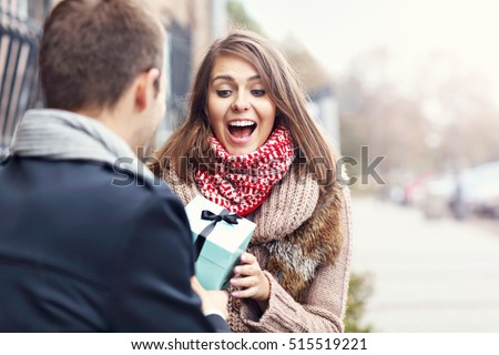 Picture showing young couple with present in the park
