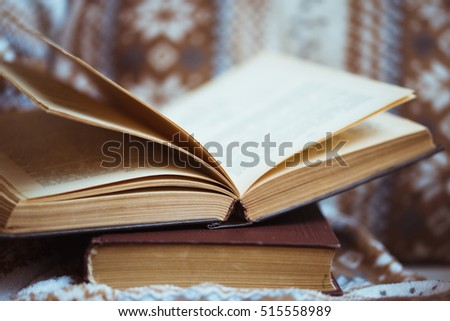 Stack of books with warm plaid on chair #515558989