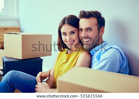 Portrait of beautiful couple in their new apartment sitting around boxes #515615566