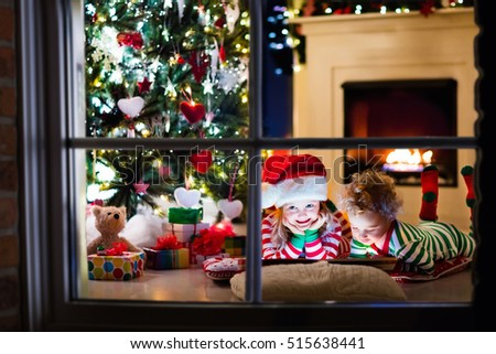 Happy little kids in matching red and green striped pajamas decorate Christmas tree in beautiful living room with traditional fire place. Children opening presents on Xmas eve. #515638441
